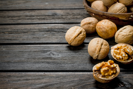 Peeled walnut. On a wooden background Imagens