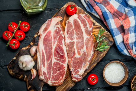 Raw pork steaks with aromatic and herbs and spices. On a black rustic background. 스톡 콘텐츠