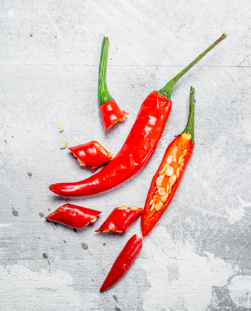 Pieces of hot red pepper. On white rustic background
