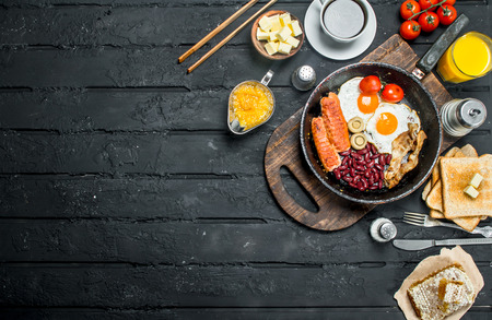 Traditional English Breakfast with fried eggs, sausages and aromatic coffee. On black rustic background.