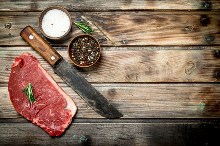 Raw marbled beef steak with spices. On a wooden background.