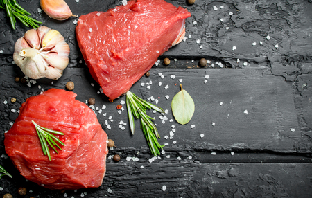 Raw meat. Sliced pieces of beef with spices and herbs on a wooden Board. On a black rustic background. Standard-Bild - 120869883