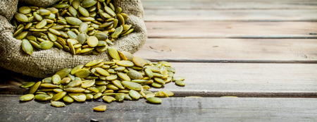 Pumpkin seeds in a bag. On a wooden background.