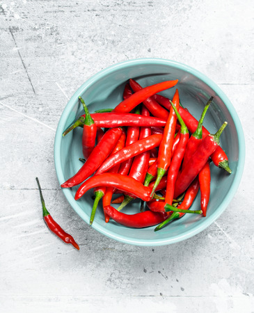 Hot pepper in bowl. On white rustic background Banco de Imagens