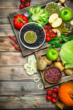 Healthy food. Healthy assortment of vegetables and fruits with legumes. On a wooden background. 版權商用圖片