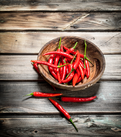 Fresh ripe red pepper in wooden bowl. On wooden background