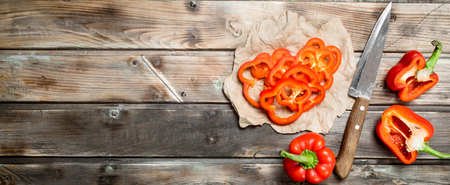 Pieces of fresh sweet pepper on paper with a knife. On wooden background