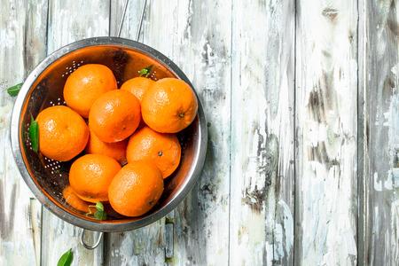 Fresh mandarins in a colander. On wooden background