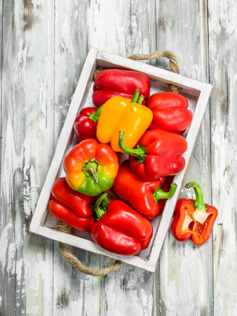 Red and yellow bell peppers on tray. On wooden background Banque d'images - 120871233