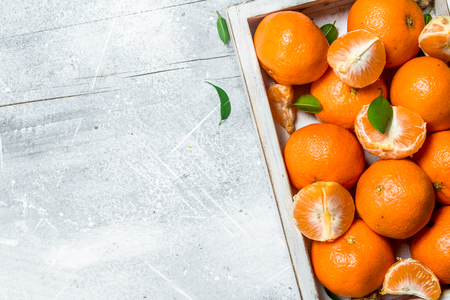 Fresh mandarins in the tray. On rustic background