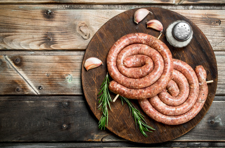 Raw sausage with rosemary and garlic. On a wooden background. Imagens