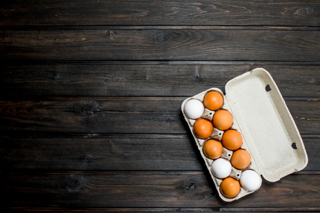 Cassette of fresh eggs. On a wooden background.