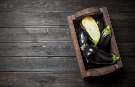 Ripe eggplant in the box. On black wooden background Imagens