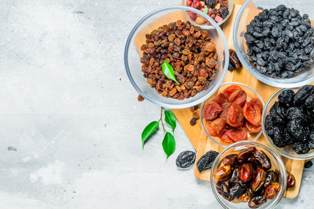 Assortment of different types of dried fruits in bowls. On a rustic background. 版權商用圖片