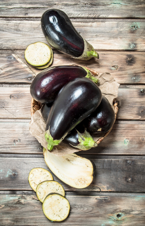 Fresh eggplant in the basket. On wooden background Imagens