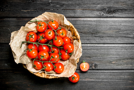 Ripe tomatoes on a branch in the basket. On wooden background 写真素材