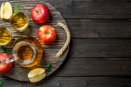 Apple juice in a glass decanter on a wooden dressing with fresh apples. On wooden background.