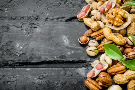 Nuts background. Different kinds of nuts with leaves. On black rustic background. Imagens - 120953623