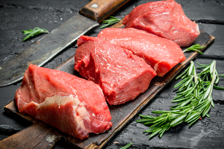 Raw meat. Pieces of beef with hatchet and rosemary branches. On a black rustic background. Standard-Bild - 120953960