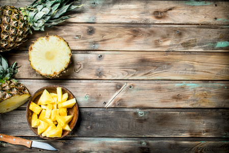 Pieces of ripe pineapple in a bowl. On wooden background