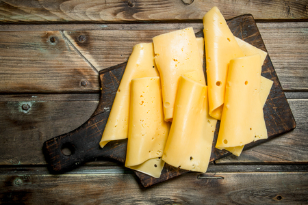 Thin slices of cheese on the cutting Board. On a wooden background. Фото со стока