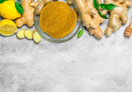 Ground ginger in a glass bowl. On rustic background Reklamní fotografie