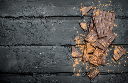 Chocolate slices sprinkled with cocoa powder. On black rustic background.
