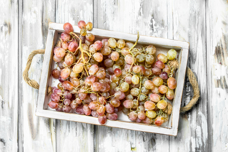 Pink grapes in the box. On a rustic background. 스톡 콘텐츠