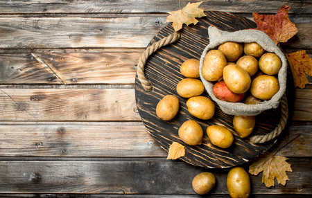 Potatoes in a sack on the tray with the leaves. On wooden background