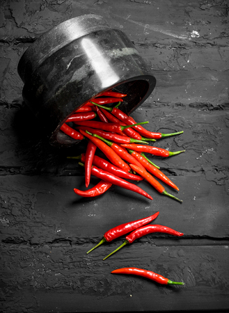 Aromatic hot pepper in bowl. On rustic background
