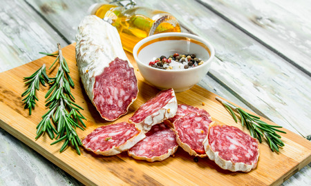 Smoked salami with rosemary and spices. On a rustic background.