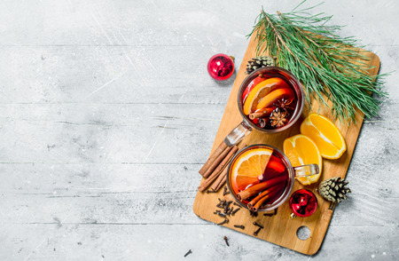 Christmas hot mulled wine with aromatic spices. On a rustic background.