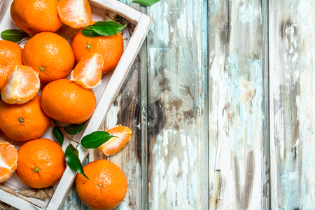 Fresh ripe mandarins with leaves in tray. On wooden background Stock fotó