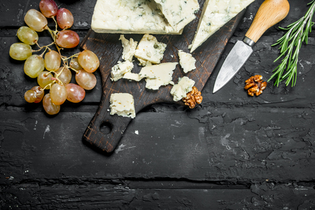 Blue cheese with grapes and rosemary. On a black rustic background.