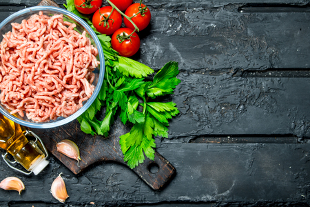 Raw minced meat in a bowl with green parsley and tomatoes. On black rustic background. Stock Photo