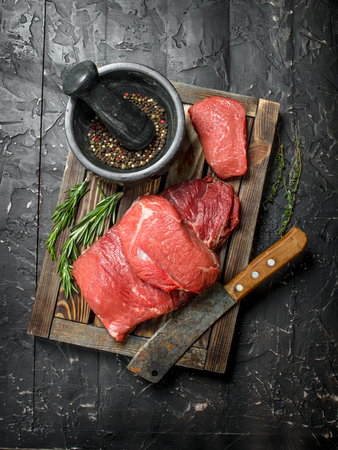 Raw meat. Fresh beef on a wooden tray with fragrant peppercorn and rosemary branches. On a black rustic background. Standard-Bild - 120871835