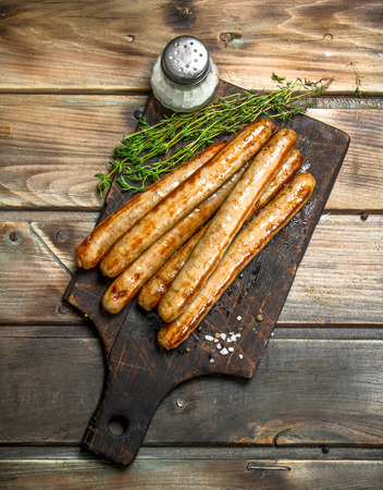 Grilled pork sausage with spices and herbs . On a wooden background. Imagens - 120871504