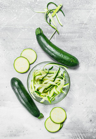 Pieces of zucchini in a glass bowl. On rustic background 免版税图像