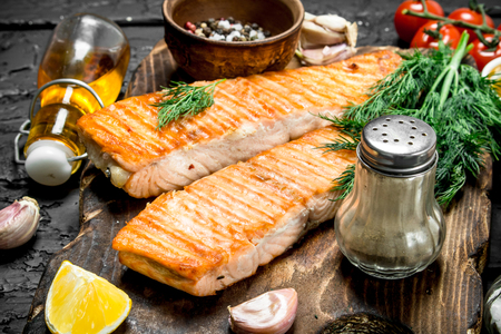 Grilled salmon fillet with spices and dill branches. On a black rustic background.
