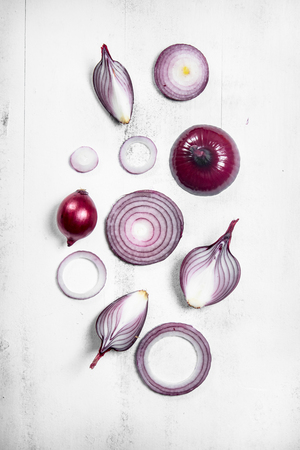 Pieces of red onions. On white rustic background Stock Photo