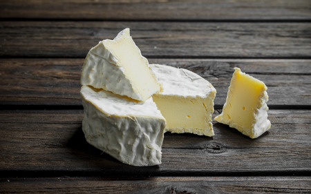 Brie cheese. On a wooden background
