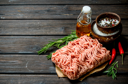 Raw minced meat with spices and herbs . On a wooden background.
