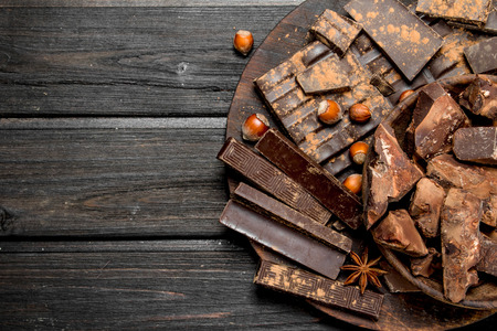 Assortment of different chocolate with nuts and cinnamon. On a wooden background.