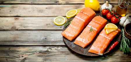 Raw salmon fish filet with lemon, tomatoes and herbs. On a wooden background.