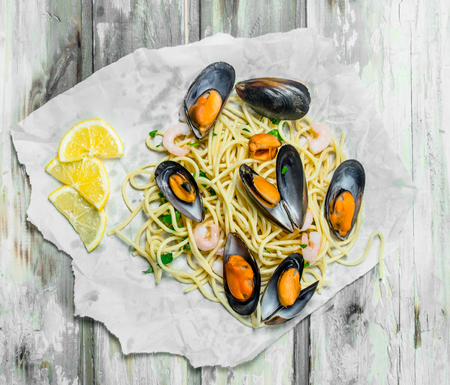 Mediterranean pasta. Spaghetti seafood with clams on paper. On a rustic background.