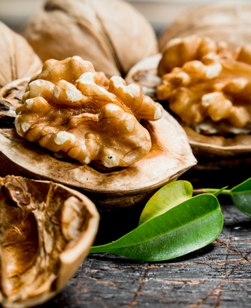 Shelled walnut with green leaves. On a wooden background. Imagens