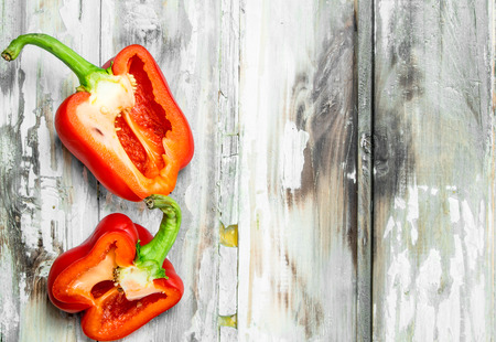 Halves of sweet fresh pepper. On wooden background