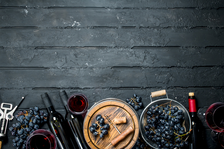 Wine background. Red wine with grapes and an old barrel. On a black rustic background.