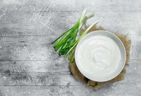 Sour cream with green onions in bowl . On a rustic background.