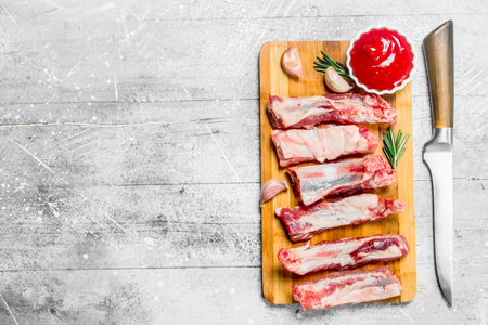 Raw ribs with tomato sauce and fragrant rosemary . On a rustic background.
